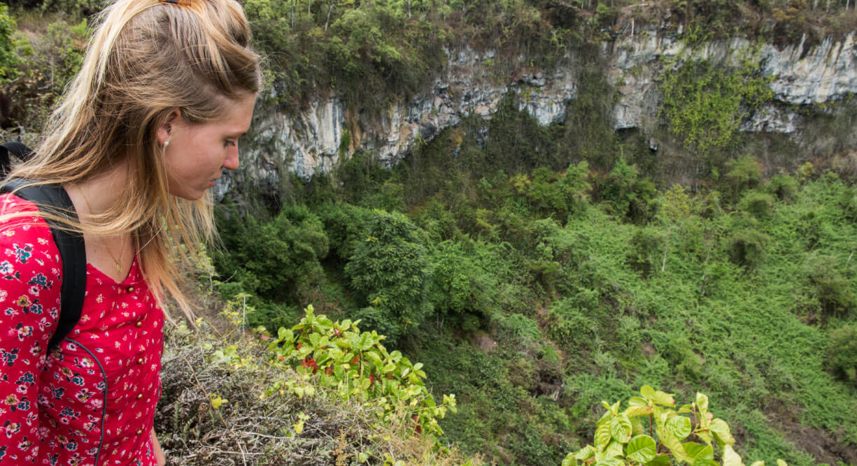 Highlands - Santa Cruz, in the Galapagos view of the crater with plants and girl tourist