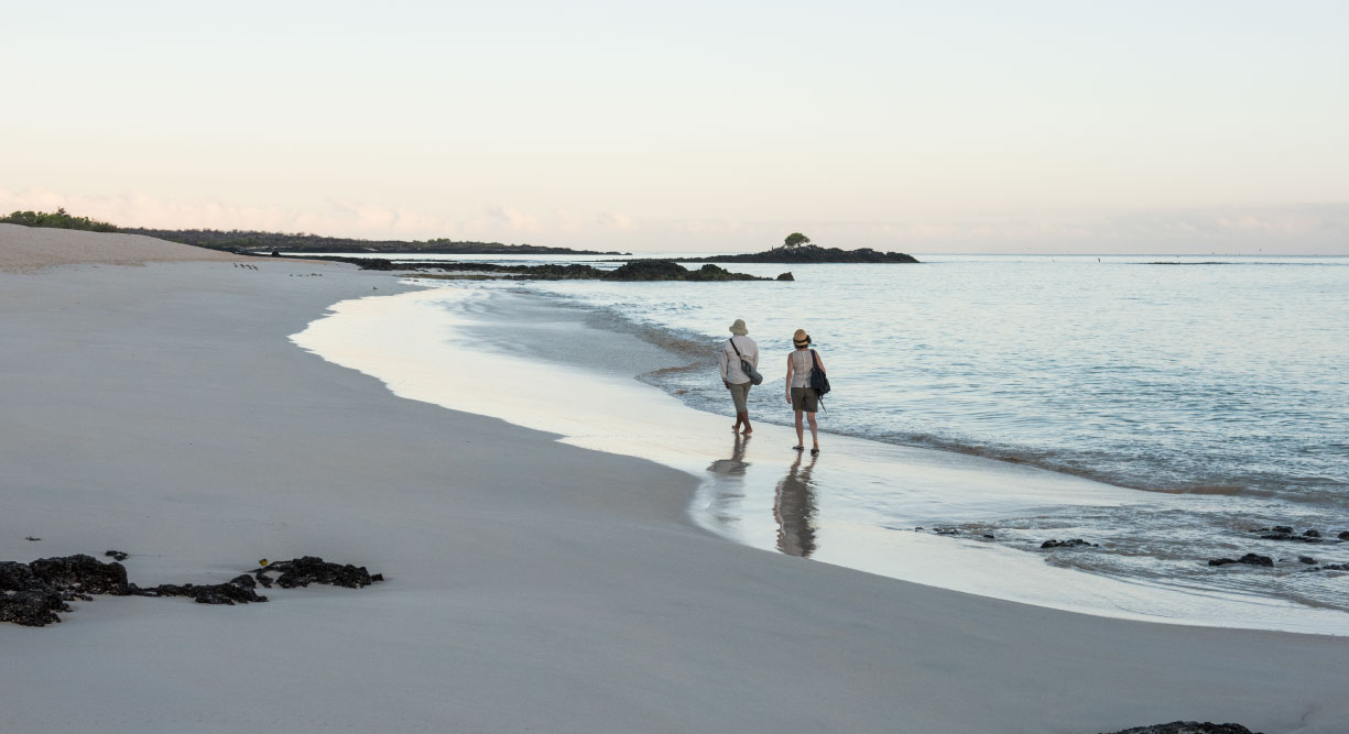 Bachas Beach - Santa Cruz in Galapagos Island beautiful white sand beach and tourist walking