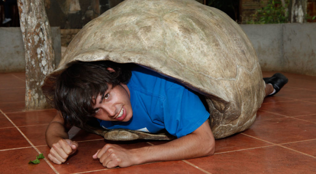 Cerro colorado - San Cristobal in the Galapagos Islands, tourist inside of giant tortoise shell