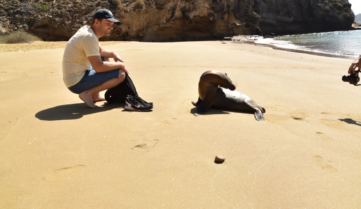 Pitt Point - San Cristobal in Galapagos Islands, tourist interacting with a sea lion in golden sand beach