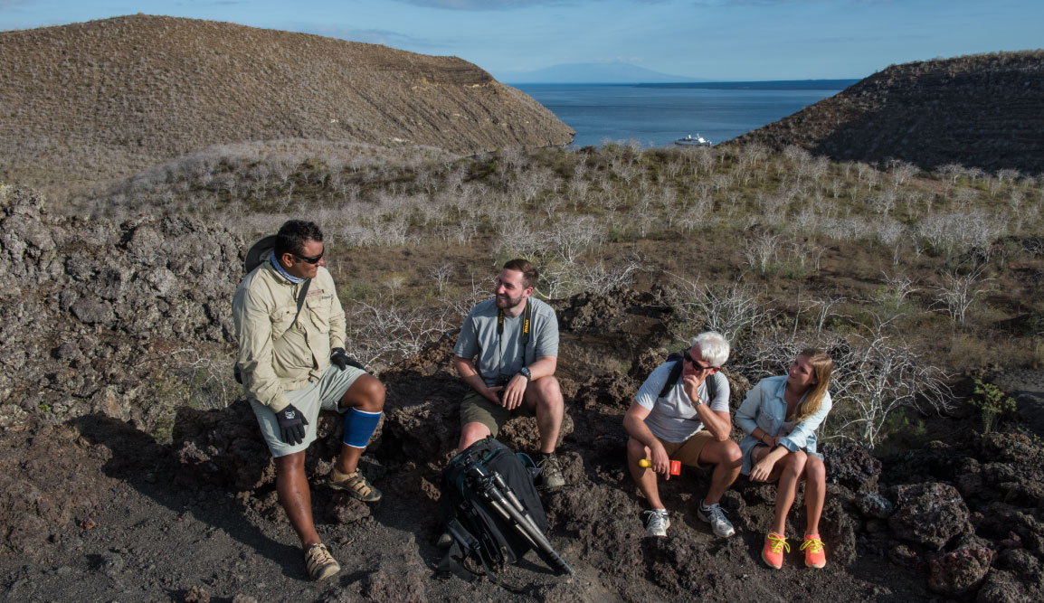 Tagus Cove - Isabela in the Galapagos Islands Itinerary B, tourist talking with a experienced guide while resting