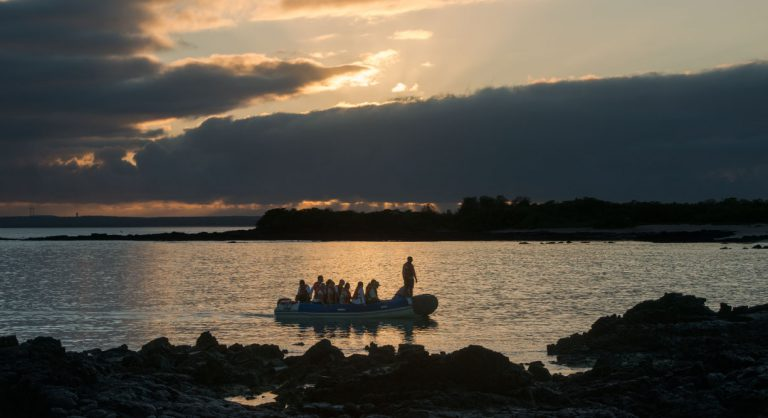 Bachas Beach - Santa Cruz in the Galapagos Islands with tourist in panga