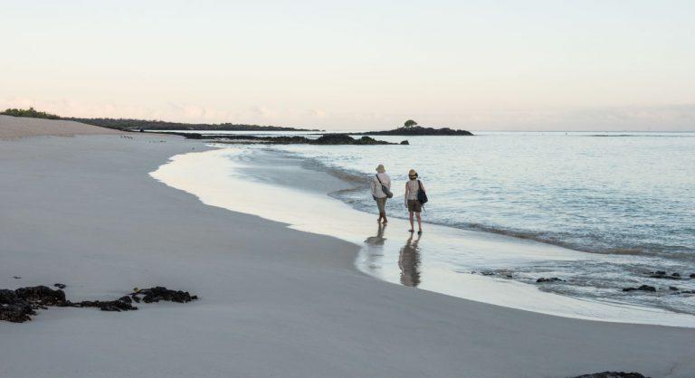 Bachas Beach - Santa Cruz in Galapagos Island beautiful white sand beach and tourist walking