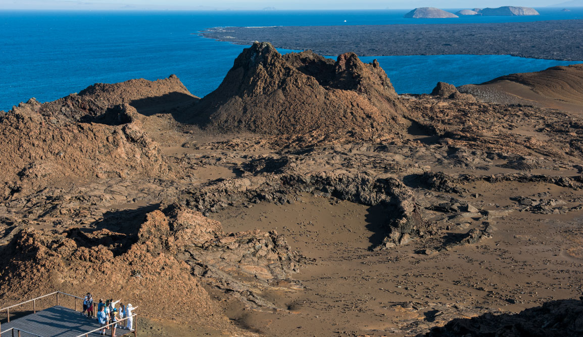 Bartolome in Galapagos Islands view of the volcanic terrain and the crater, with tourist taking pictures