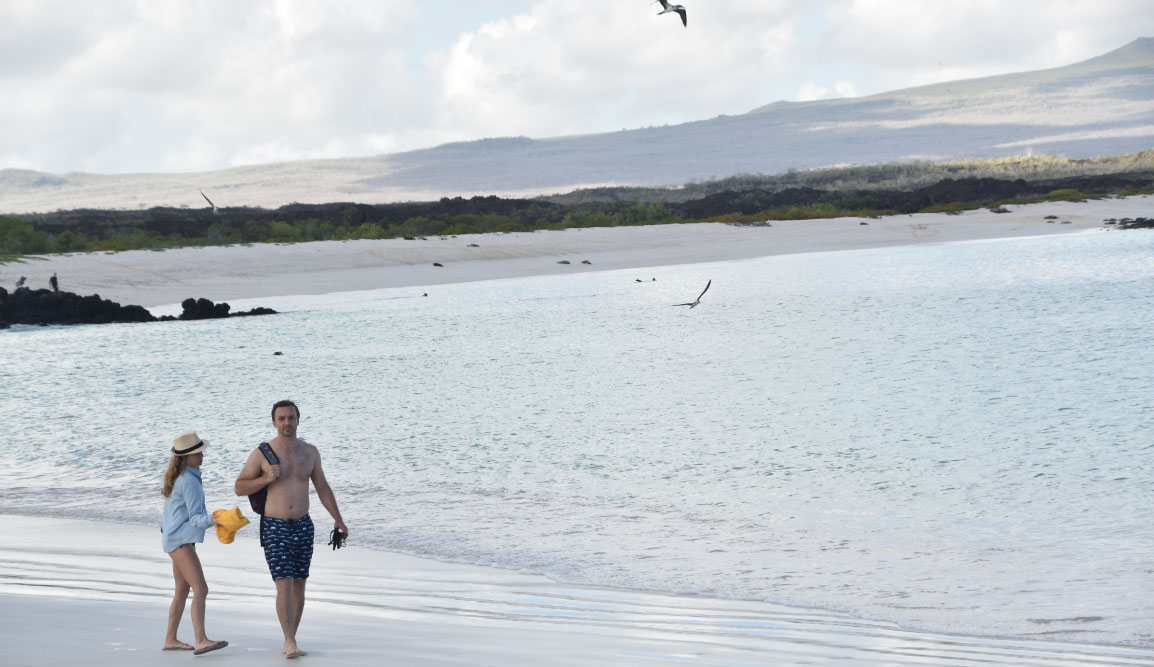 Cerro Brujo - San Cristobal in Galapagos Islands, tourist walking in the beach and watching the sea