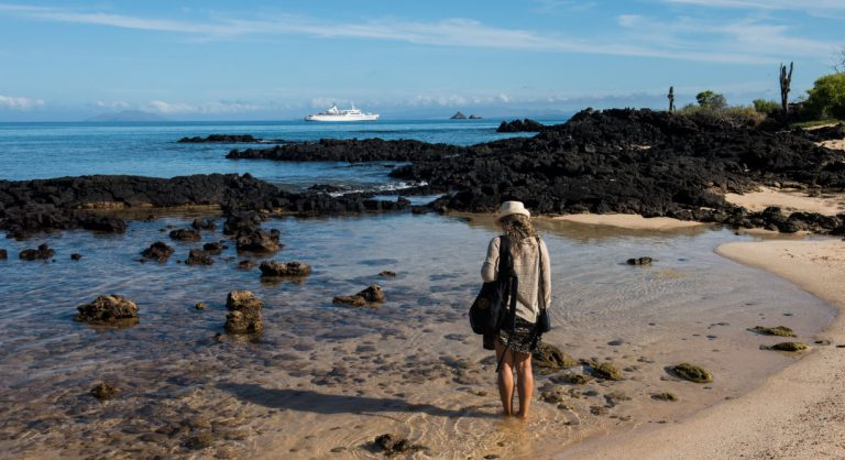 Dragon Hill - Santa Cruz in the Galapagos Islands, view of volcanic beach and tourist walking on the seashore