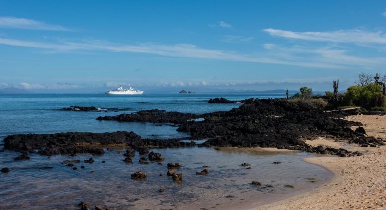 Dragon Hill - Santa Cruz in the Galapagos Islands, view of volcanic beach and the Galapagos Legend in the sea