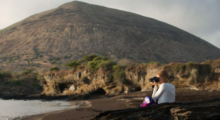 Egas Port in Santiago Island wit rocky beach and tourist taking pictures, background of volcano