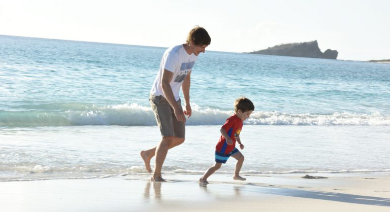 Gardner Bay - Española in the Galapagos view of the white sand beach with tourist play with child