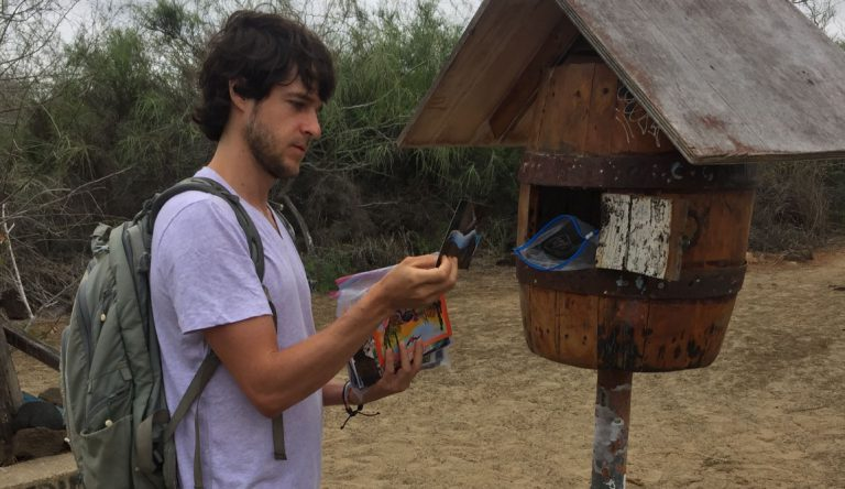 Post Office - Floreana Island in the Galapagos, tourist showing letters
