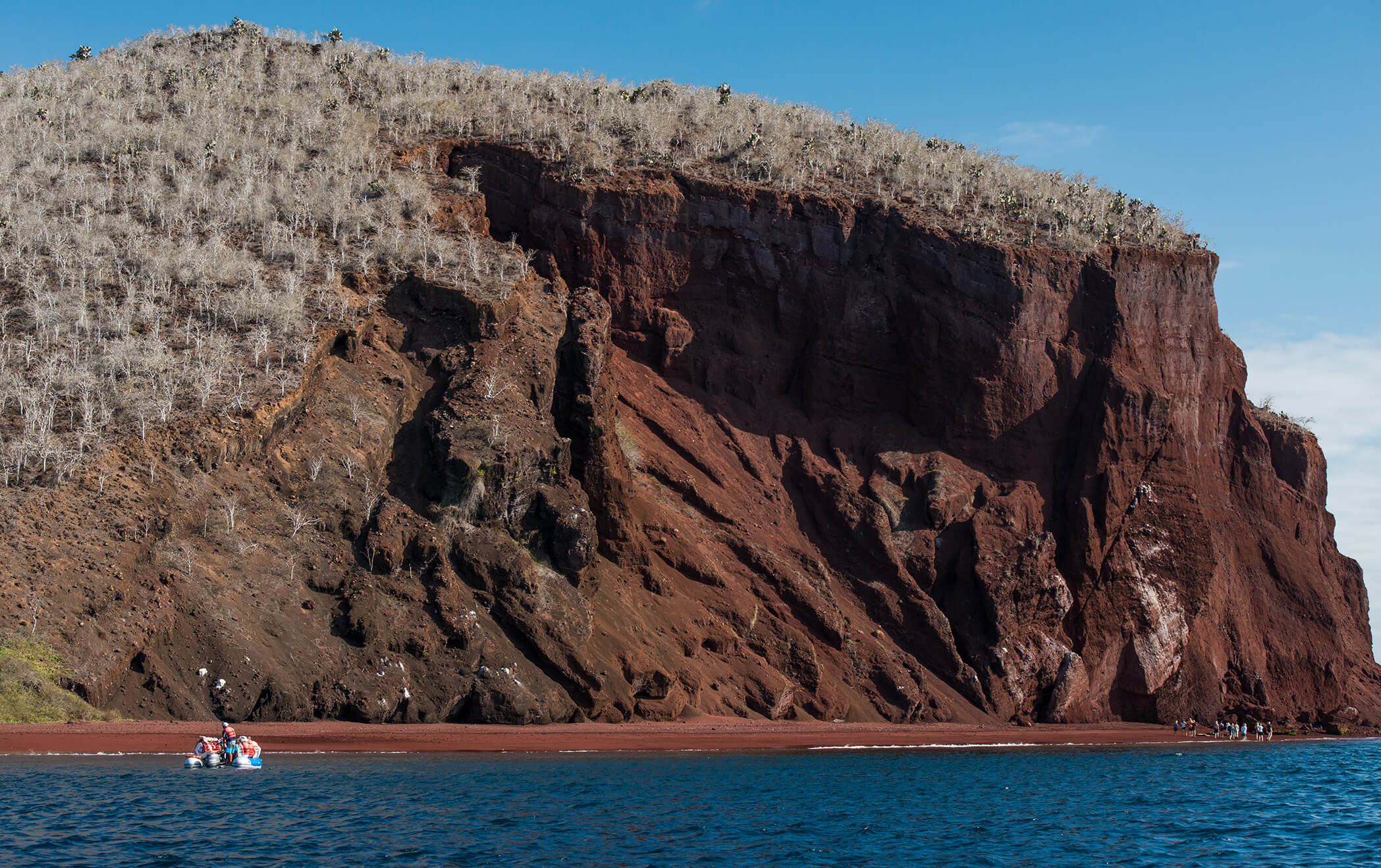 Rabida in Galapagos Islands, view of the red sand and hill with tourist wallking near to the boat