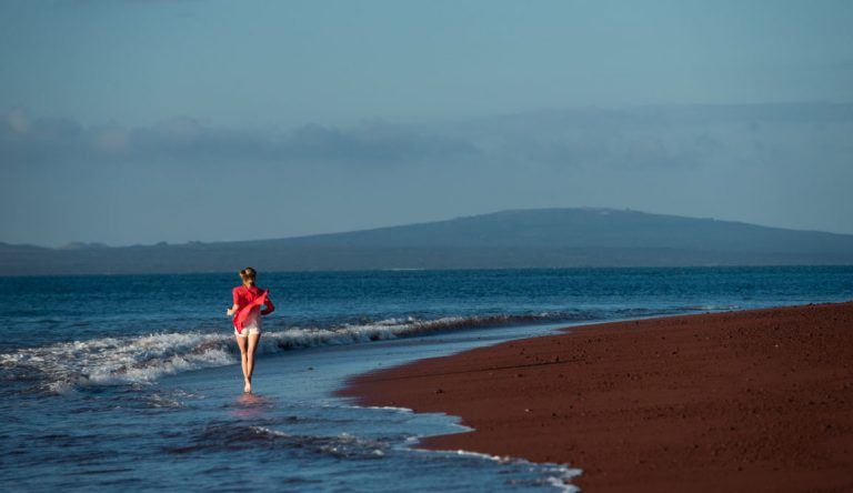 Rabida in Galapagos Islands with a red sand beach and a tourist girl jogging