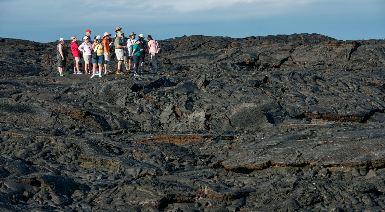 Sullivan bay in Santiago Island have a solid volcanic lava with tourist exploring the terrain