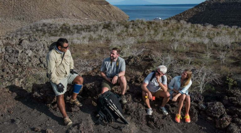 Tagus Cove - Isabela in the Galapagos Islands, tourist talking with a experienced guide while resting