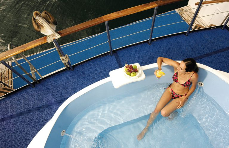 Tourist in the Jacuzzi on the Coral Yachts with a cocktail and pelican